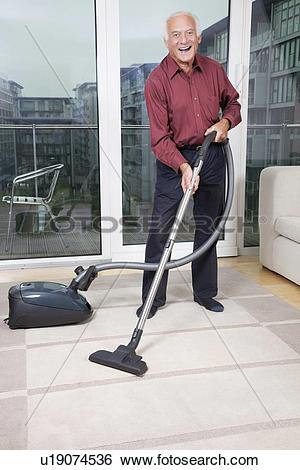 Stock Images of Portrait of happy elderly man cleaning rug with.
