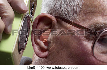 Stock Photograph of Man putting speaker to hearing aid blm011109.