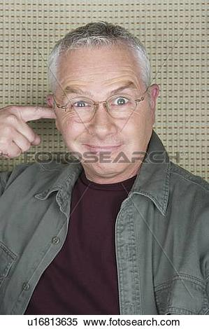 Stock Image of Older man putting finger in ear u16813635.
