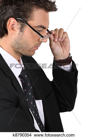 Stock Photo of businessman putting on his glasses k8790354.