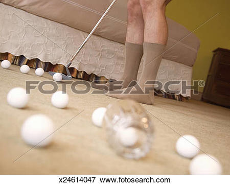 Picture of Senior man putting into glass on carpet, wearing socks.
