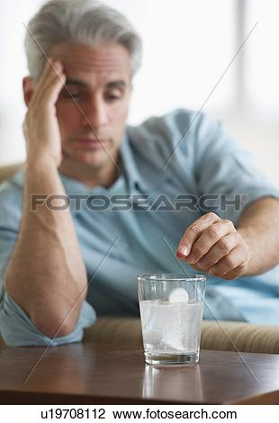 Stock Photo of Man with a headache putting medicine in glass of.