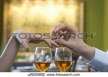 Stock Photo of Man putting engagement ring on woman's finger above.