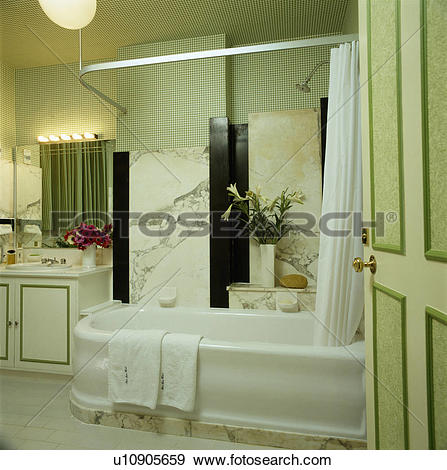 Stock Photograph of Marble wall above white porcelain bath with.