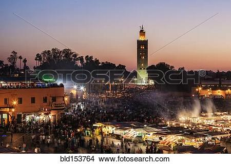 "Stock Photo of ""Illuminated mosque tower over outdoor market."