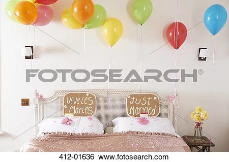 Stock Images of Decorated marriage bed with balloons and signs 412.