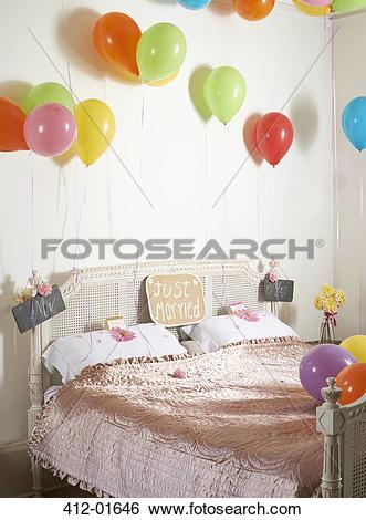 Stock Images of Colorful balloons over marriage bed 412.