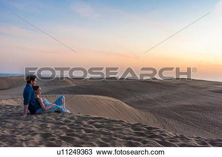 Stock Photo of Romantic mid adult couple sitting on dunes.