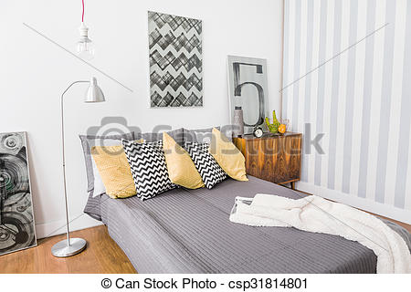 Stock Photography of Matrimonial bed with grey bedding.