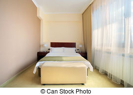 Stock Photography of Empty hotel room for two with matrimonial bed.
