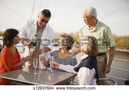 Stock Photo of Matures enjoy champagne on boat deck x12637604.