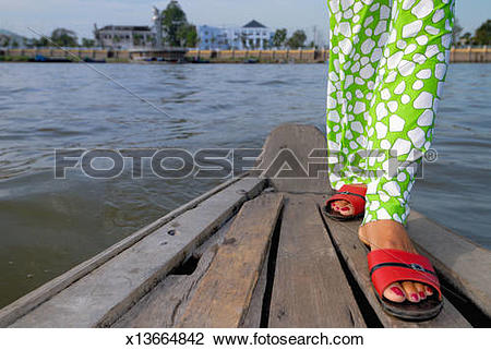 Stock Photo of Woman on small boat crossing Mekong river, low.