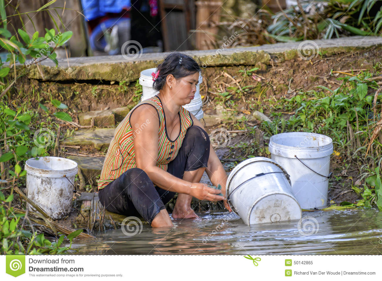 Woman Washing Dishes In Mekong River Editorial Image.