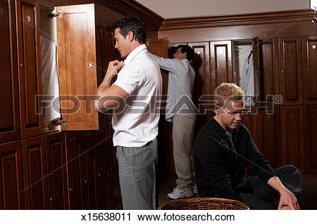 Stock Photography of Three men getting dressed in locker room.