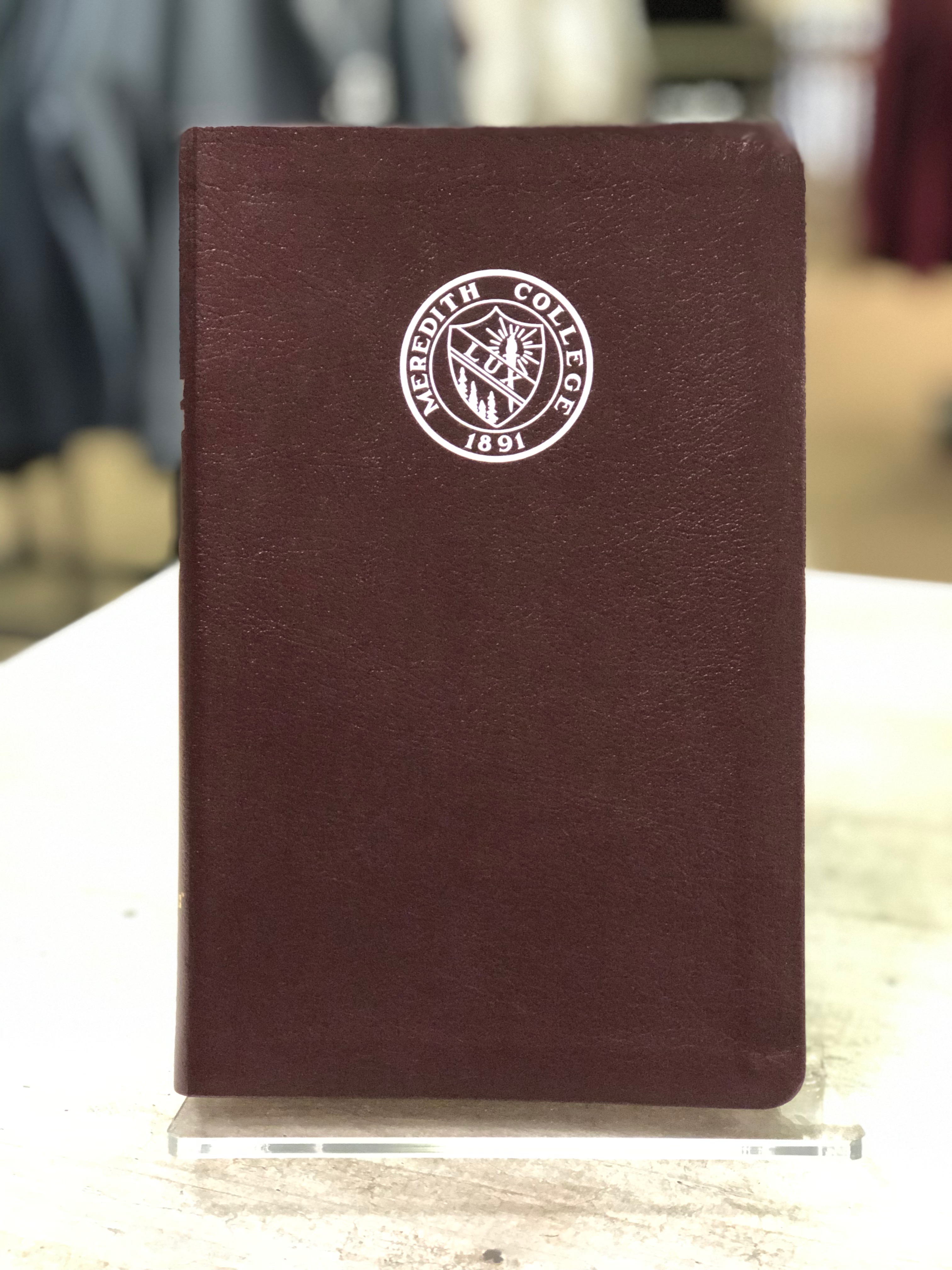 Bible with Meredith College Logo.
