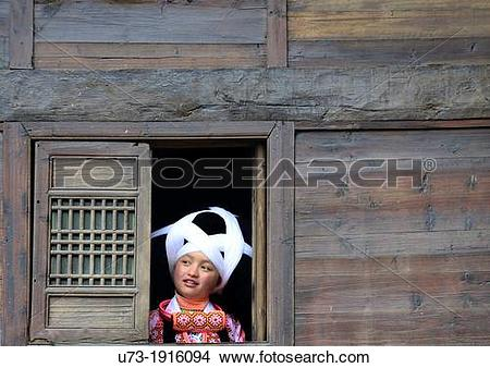 Stock Photo of A Long Horn Miao girl looking out the window of her.