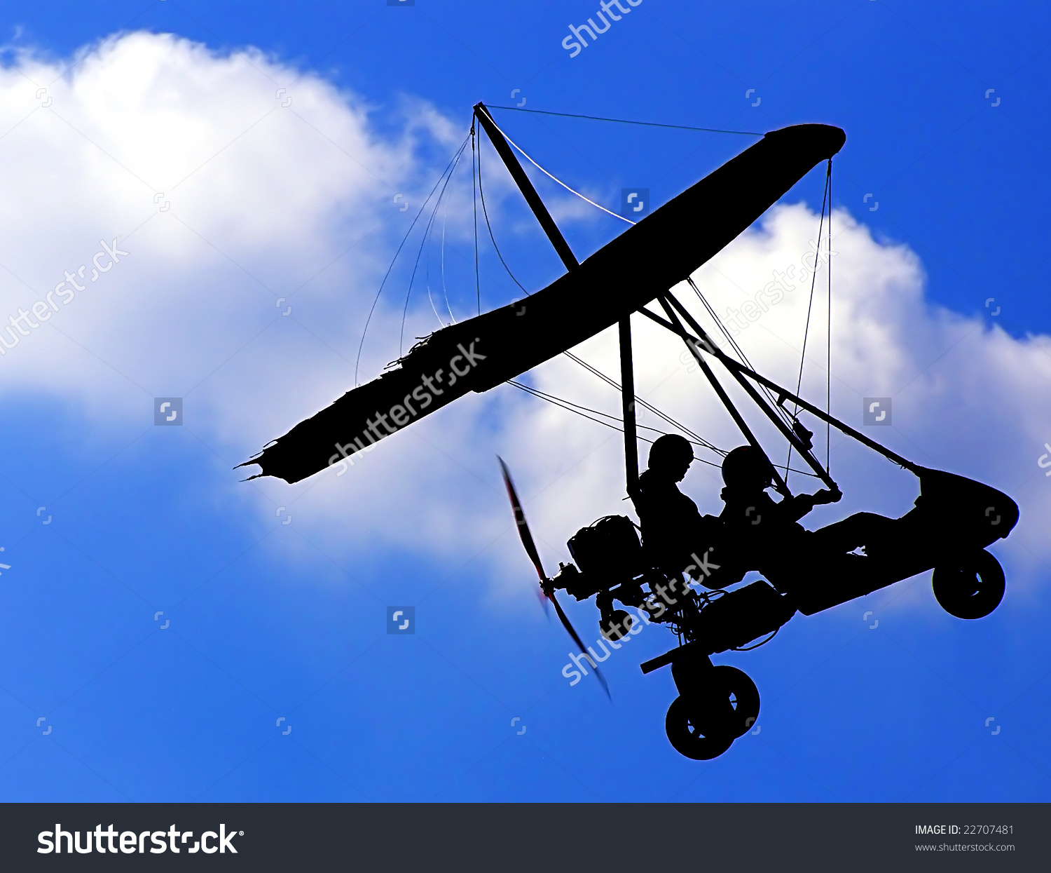 Silhouette Of The Microlight Glider In The Blue Sky Stock Photo.