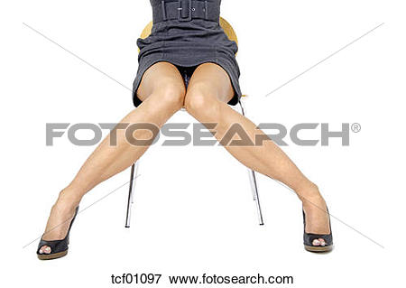 Picture of Young woman in mini dress sitting on chair, middle.