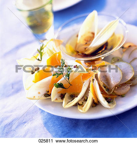 Stock Photography of Chicory salad with pears and Mimolette cheese.