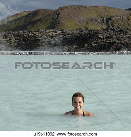 Stock Photo of Smiling woman in bathing suit submerged in.