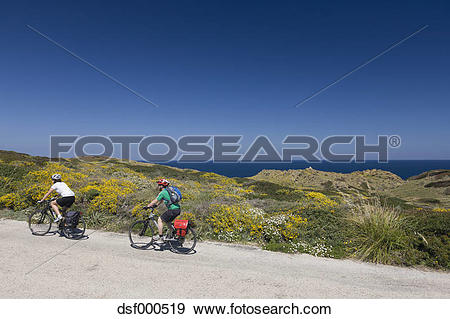 Stock Photograph of Spain, Minorca, Man and woman cycling by sea.