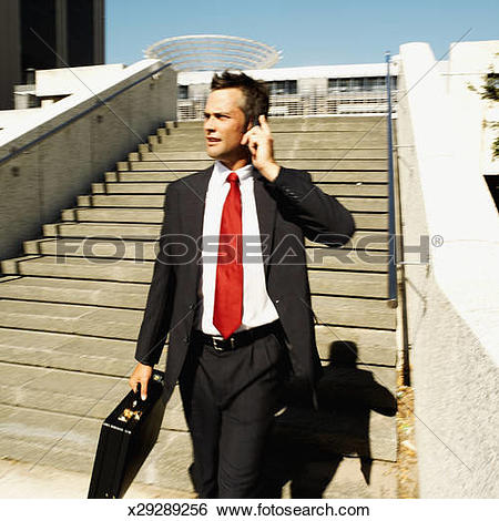 Stock Images of Businessman walking down the stairs talking on his.
