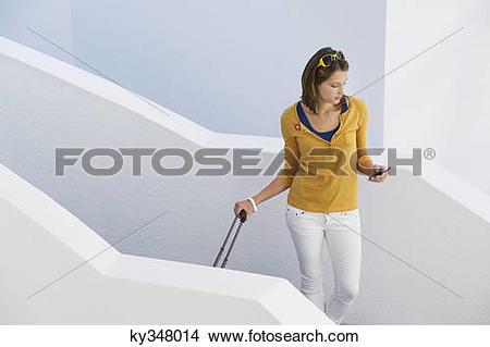 Stock Photo of Woman using mobile phone while walking down stairs.