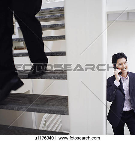 Stock Photography of Low section view of a man walking down stairs.