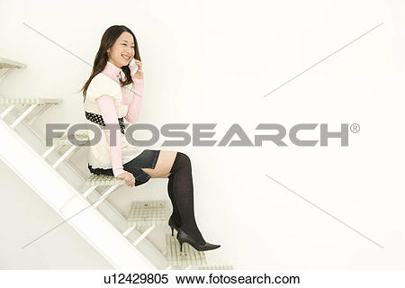 Stock Image of A woman sitting on stairs and using a mobile phone.