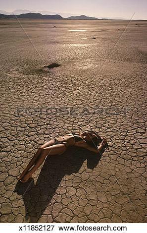 Picture of USA, California, Mojave Desert, woman in bikini lying.