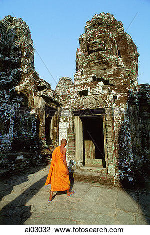 Stock Photo of Cambodia, Angkor Thom, monk walking between face.