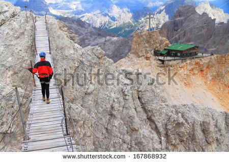 Mountaineer Crossing Suspension Bridge On Monte Stock Photo.
