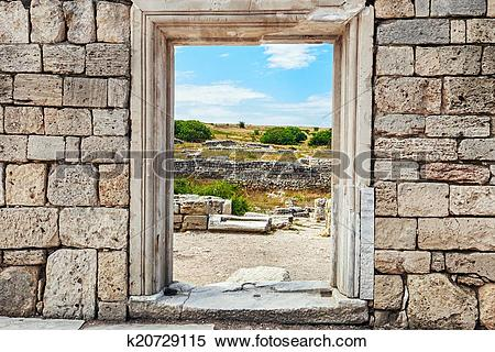 Stock Image of wall of stones with a hole under the door. Cultural.
