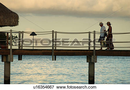 Picture of A mid adult couple walking on a pier, Moorea, Tahiti.