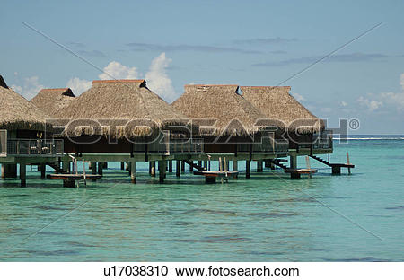 Stock Photography of Thatched buildings on stilts built in the sea.