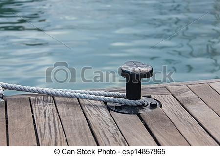 Stock Image of Mooring rope tied around steel anchor.