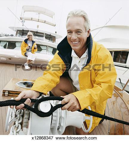 Picture of Mature Man Fastens the Mooring Rope of a Sailing Boat.