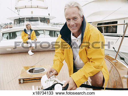 Stock Photo of Mature Man Fastens the Mooring Rope of a Sailing.