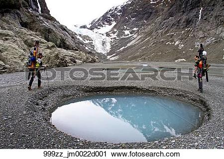 Stock Photography of Male skiers hiking with skis around a moraine.