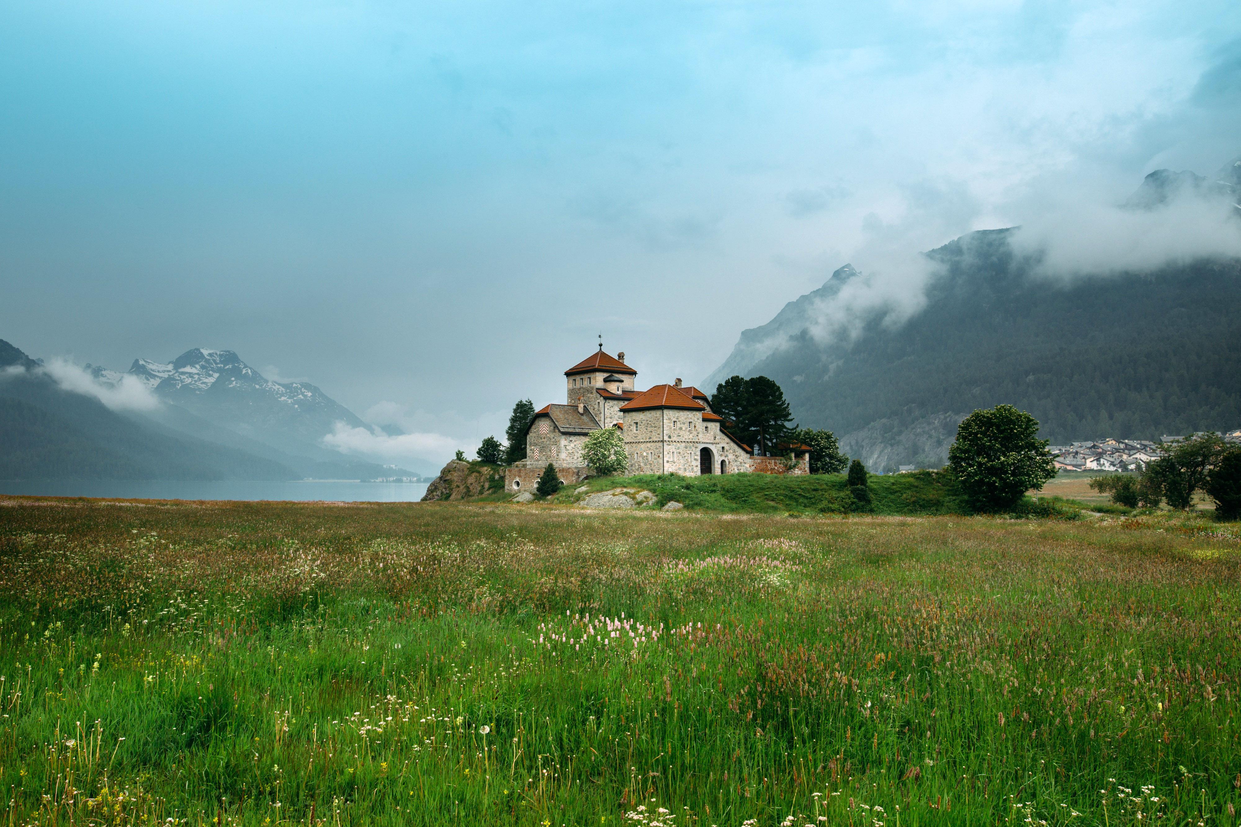Castle on the end of a grassy field in Saint Moritz, Switzerland.