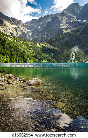 Stock Photo of Mountain lake in summer on the background of rocky.