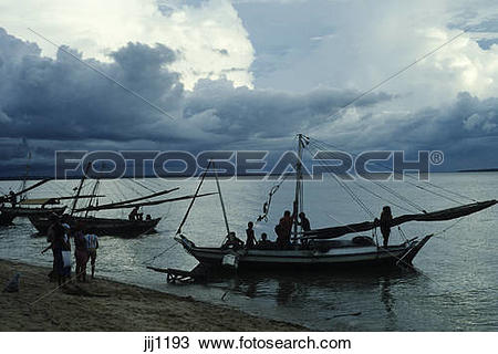 Stock Photo of Silhouette of fishing boats returning at dusk under.