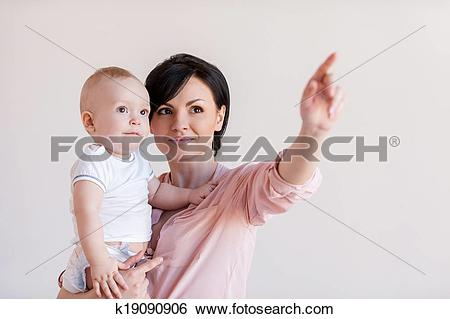 Stock Images of Look over there! Beautiful young mother holding.