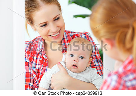 Stock Photography of mother and baby look in the mirror at home.