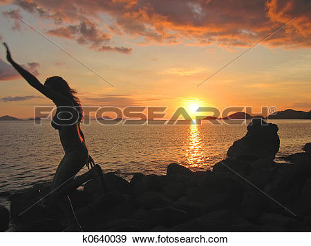 Stock Photograph of A woman in motion from profile at the sunset.