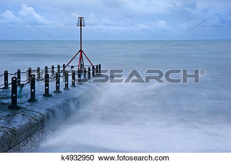 Stock Photography of Wave breaks over and floods beach beacon.