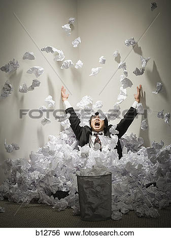 Stock Images of Businessman buried in mountain of crumpled papers.