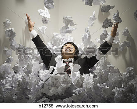 Pictures of Businessman buried in mountain of crumpled papers.