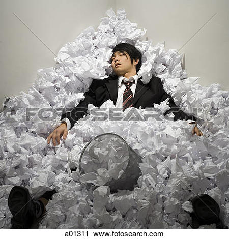 Stock Photo of Businessman buried in mountain of crumpled papers.