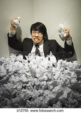 Stock Image of Businessman buried in mountain of crumpled papers.